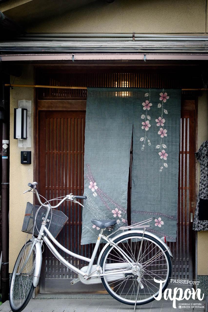 Vélo et noren à l'entrée d'une maison sur le chemin de la philosophie, préfecture de Kyoto